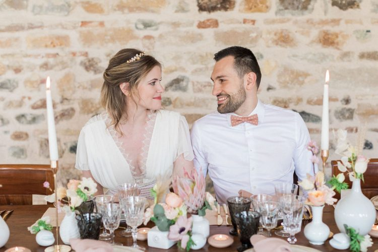 relaxed rustic french wedding couple seated at table with modern blush and peach floral details and cut glassware