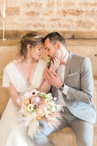 bride in french lace wedding dress and groom in grey lounge suit and bow tie wedding bouquet with roses, ranunculus, anemones, pampas grass and king protea