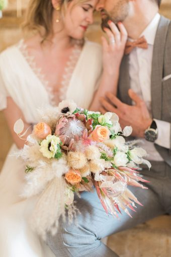 rustic french wedding bouquet with roses, ranunculus, anemones, pampas grass and king protea