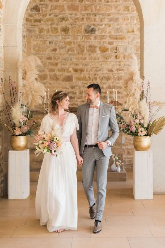 bride in french lace wedding dress and groom in grey lounge suit and bow tie surrounded by vases of rustic flowers