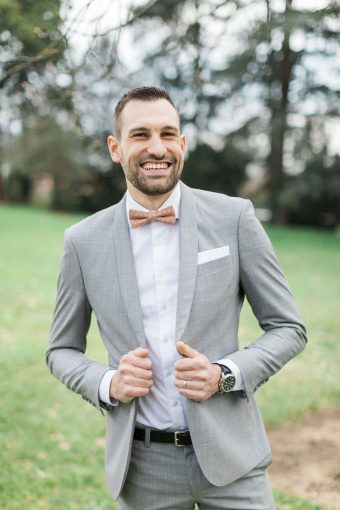 groom in grey lounge suit and bow tie