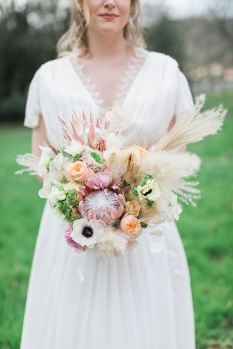 wedding bouquet with roses, ranunculus, anemones, pampas grass and king protea