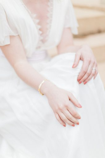 bride in french lace wedding dress with half-up hair and delicate gold bracelet