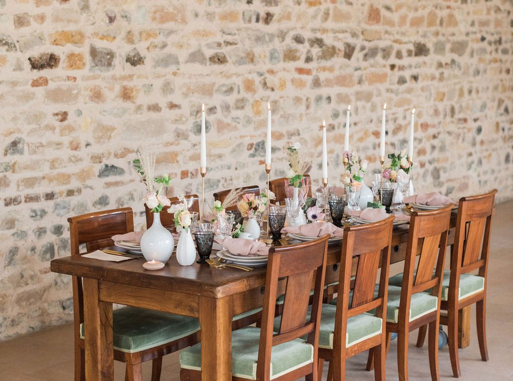 rustic french wedding table with candles and vases of blush and peach flowers with pampas grass